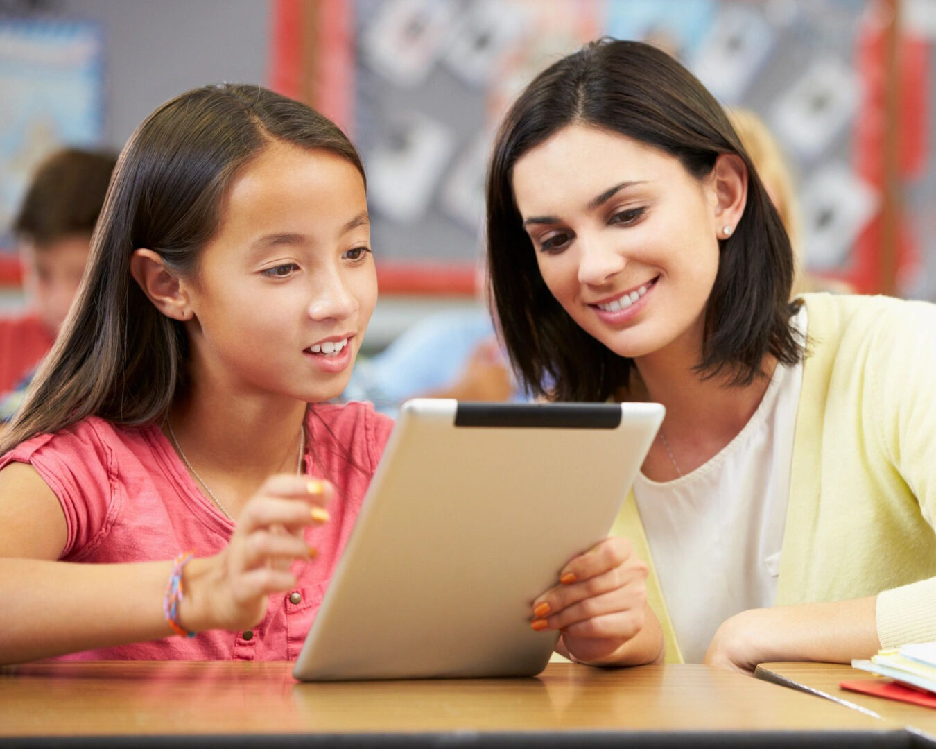 An adult woman and a girl looking at an iPad